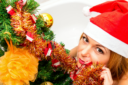nude christmas: Portrait of a beautiful woman in Santa hat near Christmas tree.