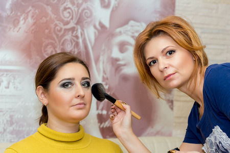 Beautiful middle-aged model, which is applied makeup. Makeup artist at work.