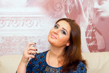 average age: Beautiful middle-aged woman applies perfume, professional make-up.