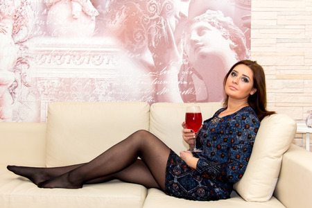 average age: Beautiful middle-aged woman sitting on the couch with glass of wine, professional make-up.