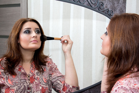 average age: Woman looking in the mirror and applies himself blush. Selective focus on the reflection. Stock Photo