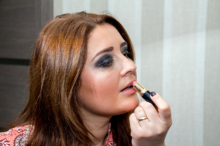 average age: Middle-aged woman applies lipstick on her lips. Beauty makeup.