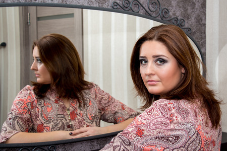 Beautiful middle-aged woman sitting near mirror, looking at camera.