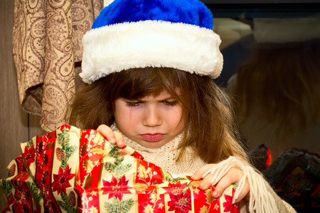 offended: Little offended girl in santa hat unwraps a gift.