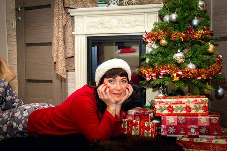 female christmas: Young beautiful woman lying on the floor near  Christmas tree.