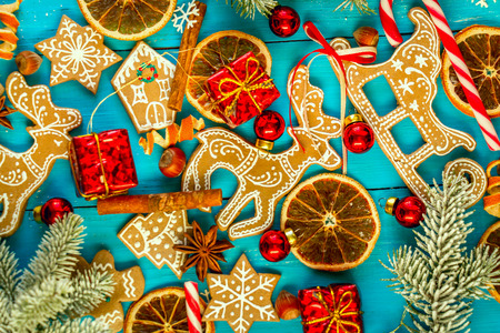 man nuts: Christmas blue wooden background with gingerbread, cinnamon, orange and balls. Stock Photo
