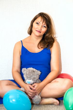 balloons teddy bear: Pregnant woman sitting on the floor with balloons and teddy bear.