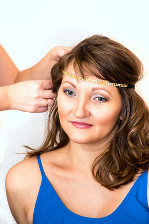 Professional hairdresser with his model on a white background. Фото со стока