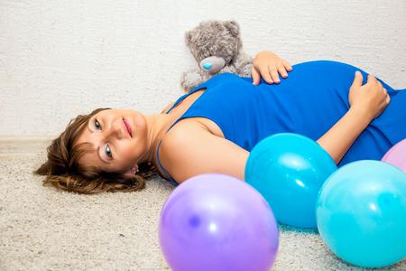 balloons teddy bear: Pregnant woman lying on the floor with balloons and teddy bear. Stock Photo