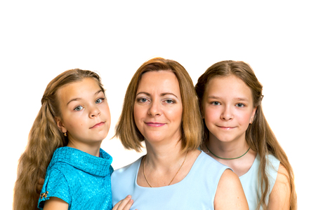 three persons only: Mother and her two daughters looking at camera. Isolated on white. Stock Photo