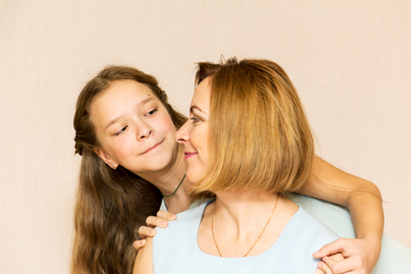 average age: Beautiful little girl hugging her mother. Family portrait.