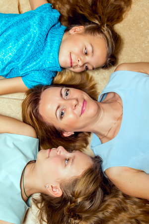 three persons only: Mother and her two daughters lying on the floor. Family portrait. Stock Photo