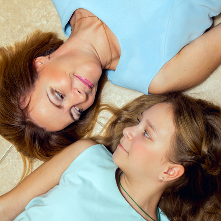 average age: Mother and daughter lying on the floor looking at each other. Stock Photo