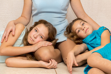 three persons only: Two girls lying on his mothers lap. Family portrait. Stock Photo