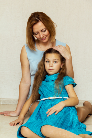 average age: Mother and daughter sitting on the floor. Family portrait. Stock Photo