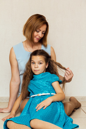 hugging knees: Mother and daughter sitting on the floor. Family portrait. Stock Photo