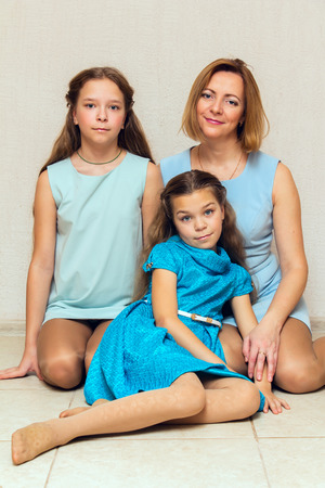 three persons only: Mother and her two daughters sitting on the floor. Family portrait.
