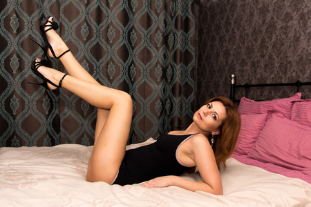 average age: Beautiful woman in underwear lying on the bed at home.