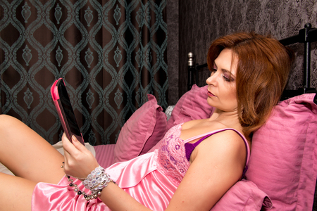 average age: Beautiful woman in underwear lying on the bed with tablet. Stock Photo