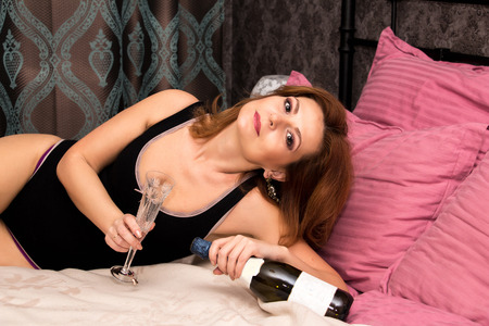 glass bed: Woman in underwear lying on a bed with a bottle of champagne and glass.