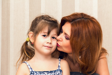 Woman kissing his little daughter. Moments of tenderness.