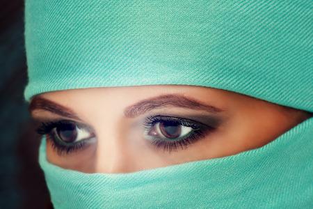niqab: Hypnotic eyes of a beautiful oriental woman in niqab, closeup. Stock Photo