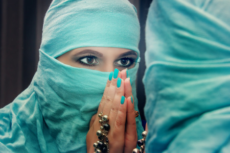 niqab: Portrait of a beautiful oriental woman in niqab, the reflection in the mirror. Stock Photo