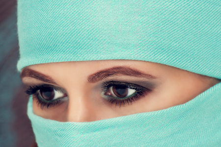 niqab: Hypnotic eyes of a beautiful oriental woman in niqab, closeup. Stock Photo