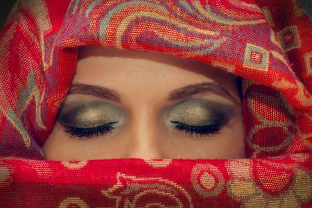 ojos cerrados: Ojos cerrados de la mujer oriental en un pa�uelo tradicional, primer plano.