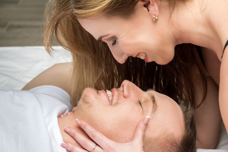 young womens: Young couple lying in bed. They are laughing. Womens hands hold a mans face.