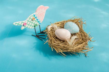 nido de pajaros: Huevos de Pascua en un nido de p�jaro sobre un fondo azul.