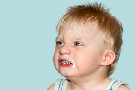 grimaces: Funny baby grimaces. Studio photography on a blue background. Stock Photo