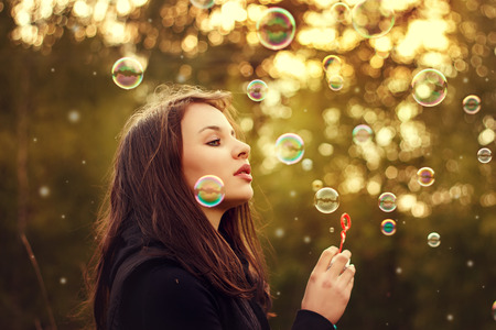 bulles de savon: Young girl blowing soap bubbles outdoors at sunset. Banque d'images