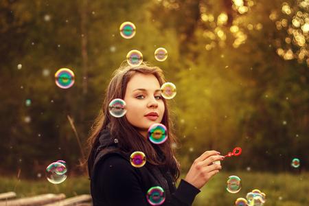 burbujas de jabon: ni�a soplando burbujas de jab�n al aire libre al atardecer.