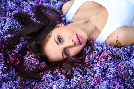 lies: Young beautiful girl lies on the lilac flowers looking at the camera. Stock Photo