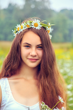 camomiles: Beautiful girl with a wreath of camomiles in the field.
