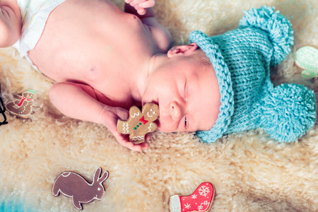 sucks: Newborn baby lying on a fur blanket and sucks gingerbread.
