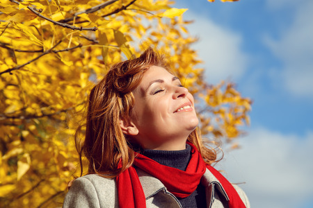 wilting: Beautiful smilling woman  in the autumn park. Bottom view.