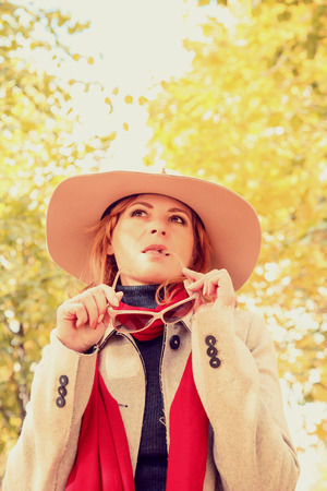 Beautiful blonde in a hat walking in the autumn park. Stock Photo