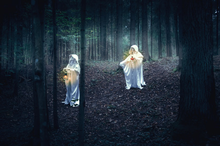 garb: Two figures in white robes with lanterns come in a dark forest.