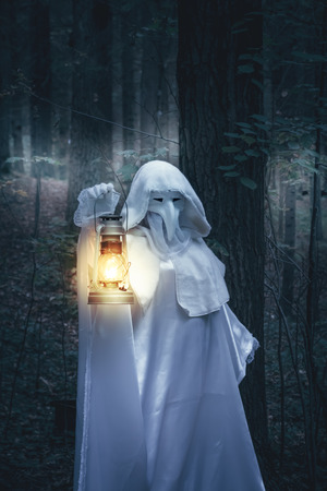come in: Figure in white robe with lantern come in a dark forest. Stock Photo