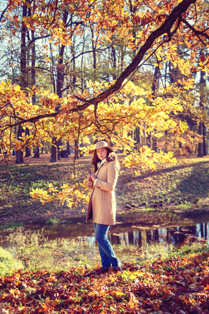 wilting: Beautiful woman in a hat walking in the autumn park.