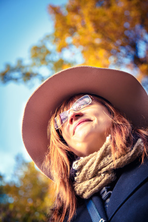 Beautiful woman in a hat walking in the autumn park. Bottom view.