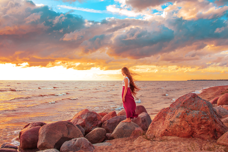 standing stone: Young beautiful girl with long hair on the seashore.