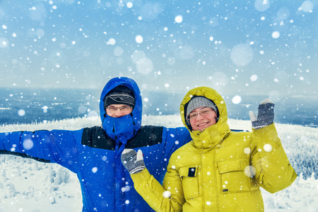 subdue: Joyful people  on a mountain top. Its snowing. Stock Photo