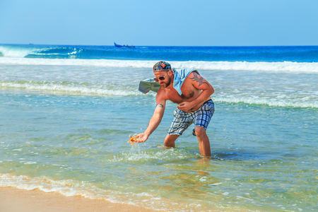 Man catches a crab on the sandy beach of the Indian Ocean.
