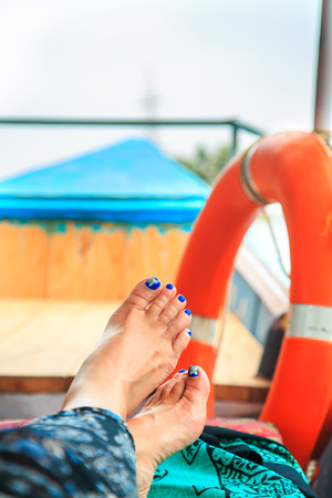 safe water: Female feet on the deck of the yacht. The concept of summer holidays.