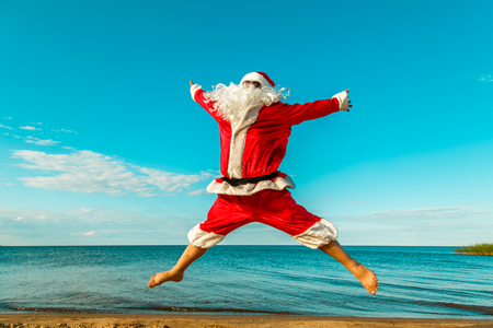 Santa Claus jumps on the beach with arms outstretched.