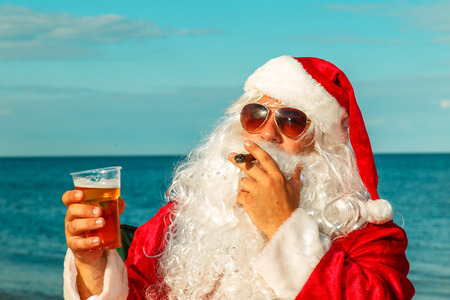Santa Claus on the beach drinks beer and smokes a cigar.