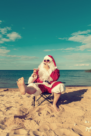 Santa Claus on the beach sits in a chair and smokes a cigar. Vintage toning.